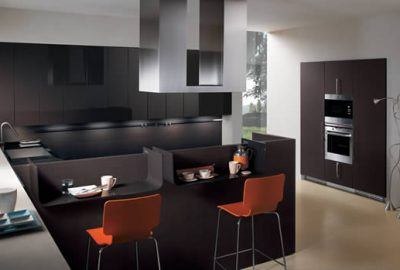 Cocina con muebles negros modernos, con desayunador y sillas rojas.