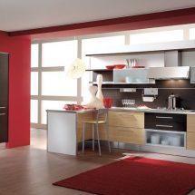 Cocina con tonos rojos, cajoneras de castaño combinadas con negro y blanco.