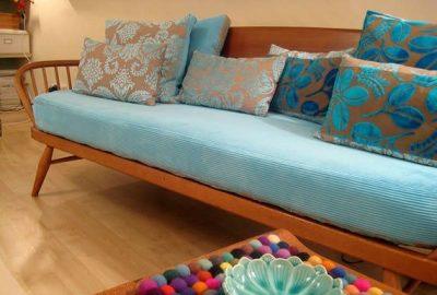 Sillon con dos combinaciones de almohadones turquesa y tierra. Con cuerpo turquesa y madera de roble.