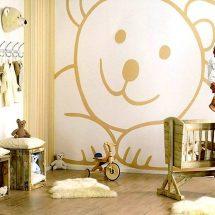 Habitación de bebé con gran stencil color beige de oso en una pared blanca.
