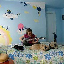 Habitación de niña con estarcido de colores aplicado sobre una pared celeste.