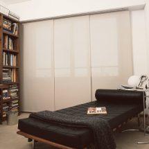 Estar con diván negro frente a un ventanal cubierto de paneles orientales