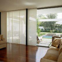 Living con gran ventanal con vista a piscina cubierto en parte por paneles orientales.