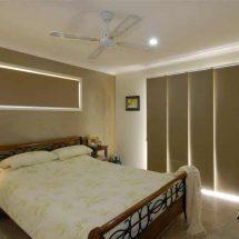 Dormitorio con gran cama en primer plano y ventanal cubierto con paneles orientales block out en color crudo