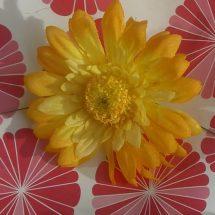 Margarita color amarillo sobre mantel rojo y blanco con flores