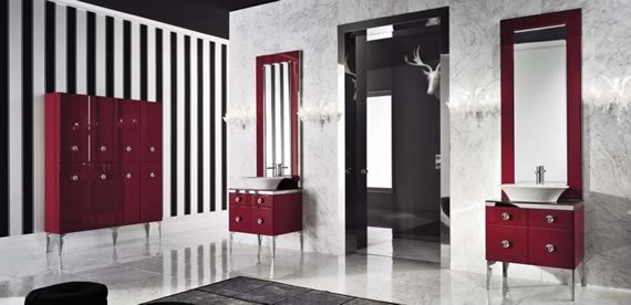Cuarto de baño con paredes a rayas blancas y negras, lavabo en color blanco sobre modular rojo con cajones. Pared independiente de mármol blanco y bordes de mármol negro.