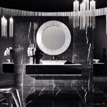 Baño negro con detalles blancos, paredes y piso de mármol, gran espejo central circular con marco de mármol blanco, lavabo blanco sobre modular en material negro brillante.
