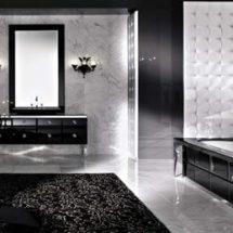 Cuarto de baño en blanco y negro con paredes de mármol, estructuras de cuero y bordes de mármol negro. Bañera y lavabo en mármol negro.