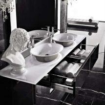 Lavabos en mármol blanco y sobre cajonera negra con cajones abiertos.