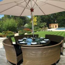 Mesa redonda con 4 sillones de ratán claro bajo parasol blanco