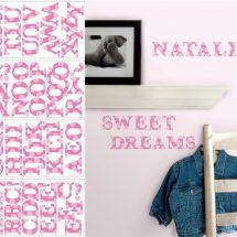 Muestra de vinilos de letras rosa sobre pared rosa más claro.