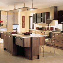 Cocina con combinación de blanco, madera oscura, negro y rojo. Isla de madera veteada, con lámpara en forma de plancha de acero, detalles en rojo en vajilla y cuadros y alzada en color negro.