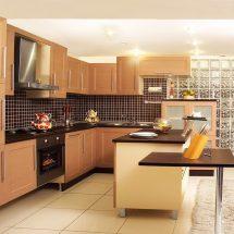 Cocina con paleta de marrones desde madera en roble y azulejos pequeños color chocolate con juntas color crema.