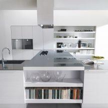 Cocina integralmente blanca y detalles de acero en los artefactos.