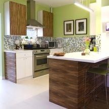 Cocina con paredes verde manzana y de la mitad para abajo venecitas en diferentes tonos de gris. Con isla, muebles combinados en blanco y madera media, artefactos de acero.