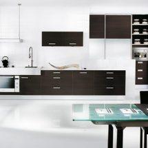 Cocina con muebles de madera oscura y artefactos en blanco.