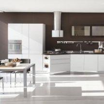 Cocina en tonos blancos, líneas simples y muebles combinados con pared en color chocolate.