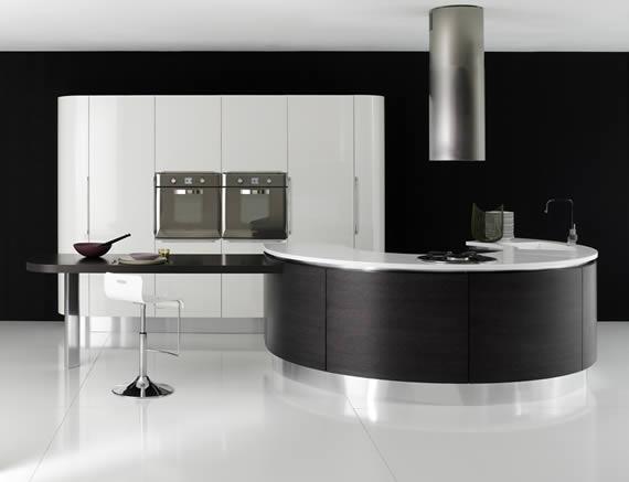 Cocina en blanco y negro, con isla en forma circular y extractor de acero sobre la misma.