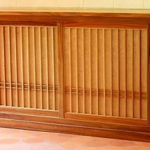 Alacena de madera natural con varillas verticales colocadas simétricamente.