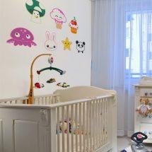 Habitación de bebe en blanco con pegatinas de diferentes personajes kawaii de muchos colores en la pared