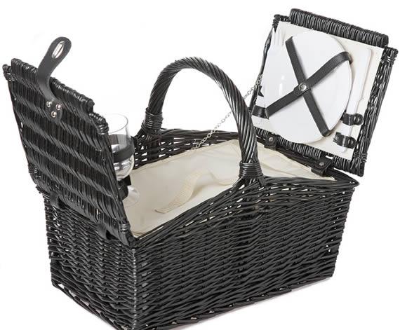 Cesta de mimbre de color negro con interior de paño blanco y vajilla blanca.